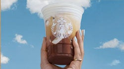 A Starbucks drink held in the air by a customer.